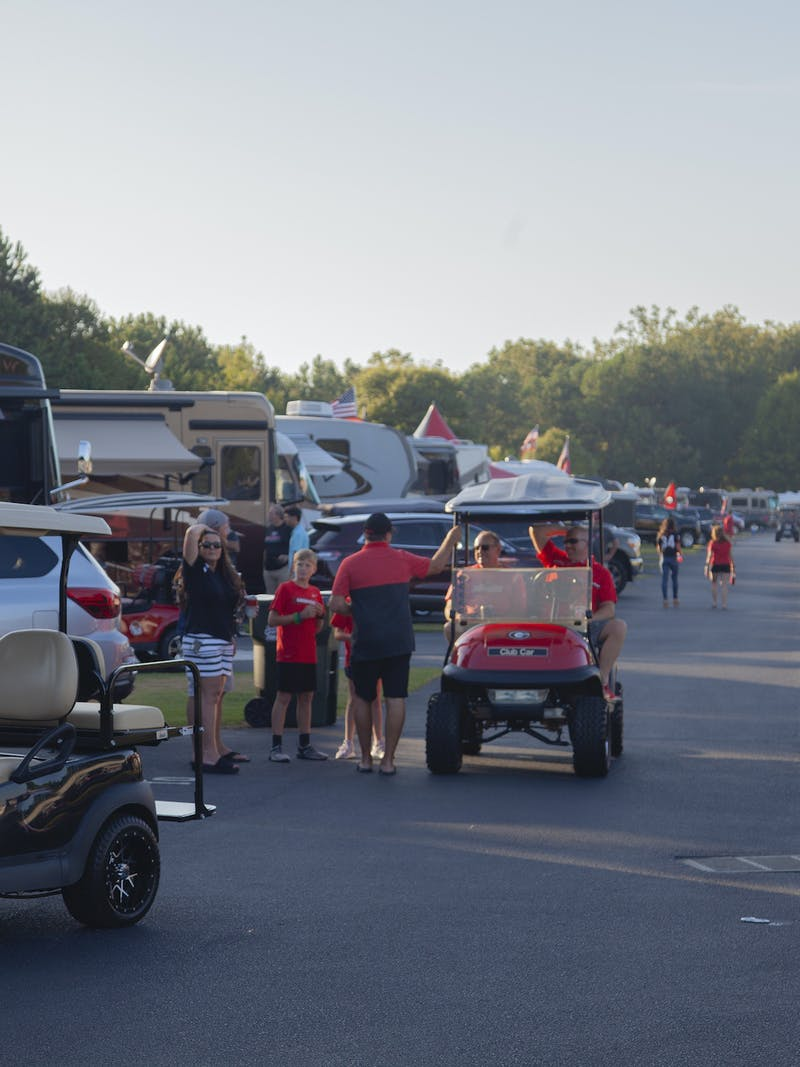 A shot of a golf cart driving down a road lined with dozens of RVs at a tailgating RV park.