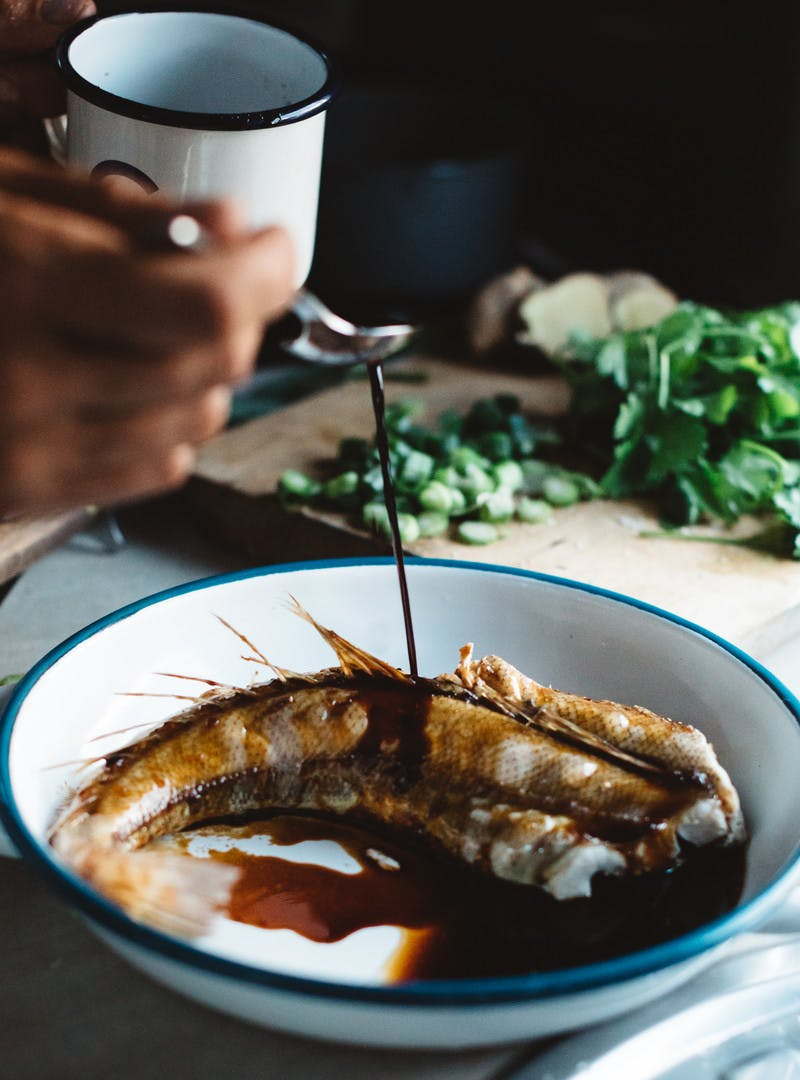 Hand drizzling marinade onto a bowl of cooked fish with cilantro in the background.