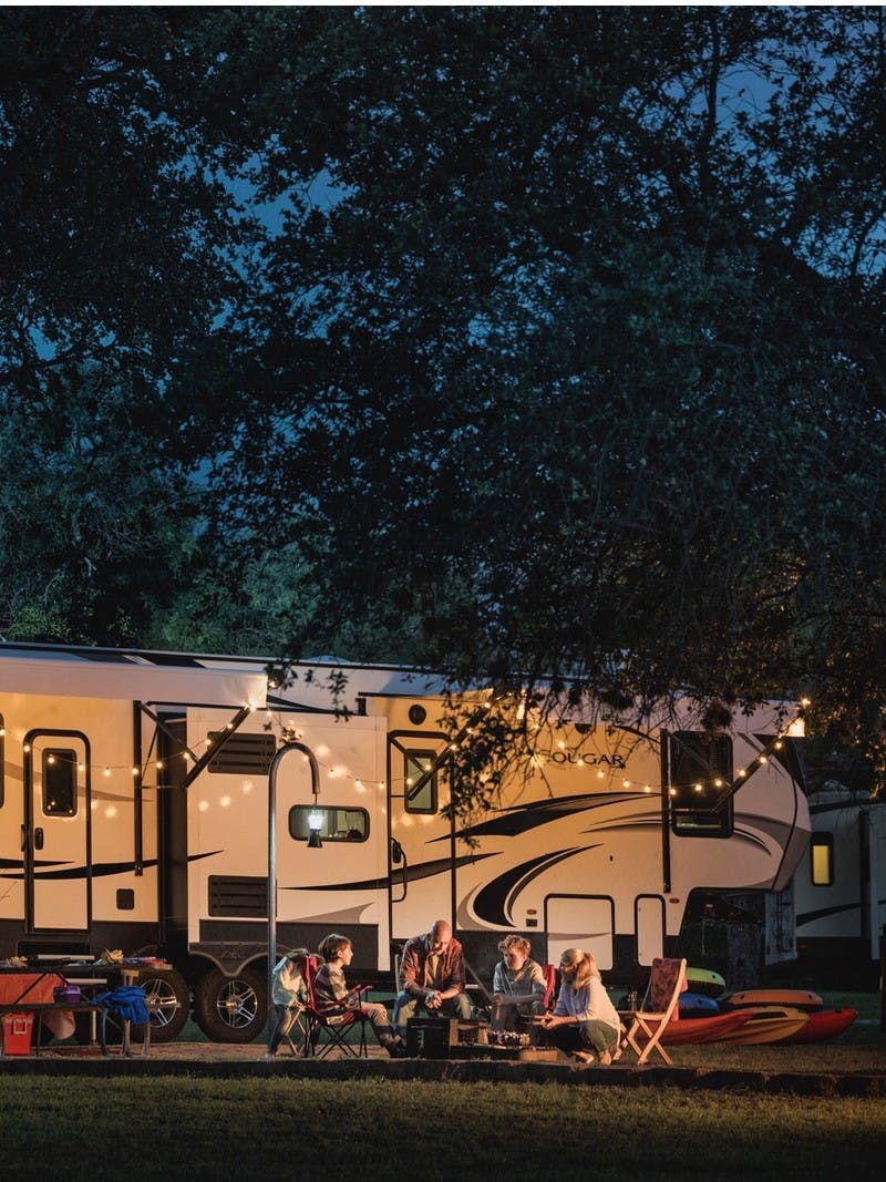 Family around campfire, in front of Keystone Cougar fifth wheel.