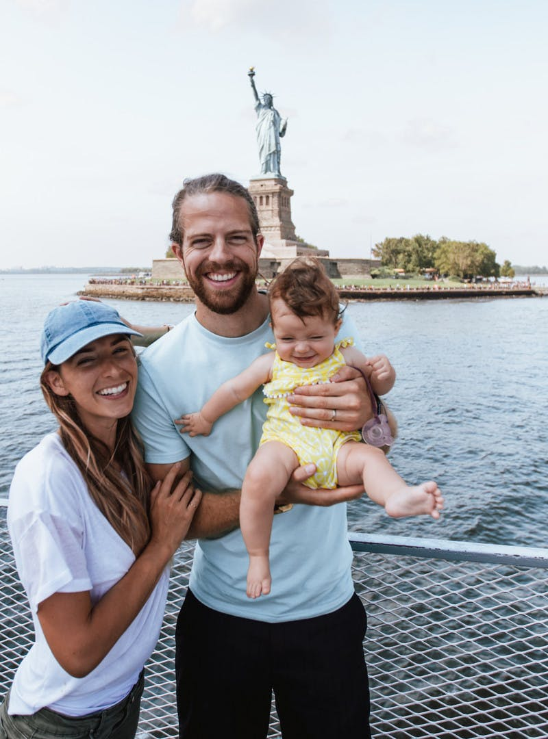 Bryce, Nellie and Avalyn Jurgy, woman and man holding a baby, on a boat, posing in front of the Statue of Liberty.