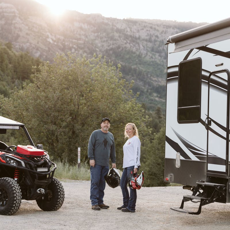 Steve & Suzanne Talbot standing next to an ATV and their Toy Hauler RV with a mountain backdrop.