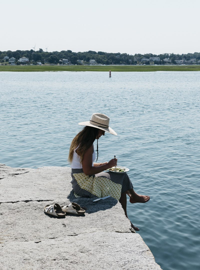 Sarah sitting on a pier, legs dangling over, eating her lunch.