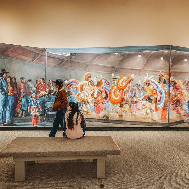 A wide shot of a museum mural depicting Native Americans in traditional and modern dress.