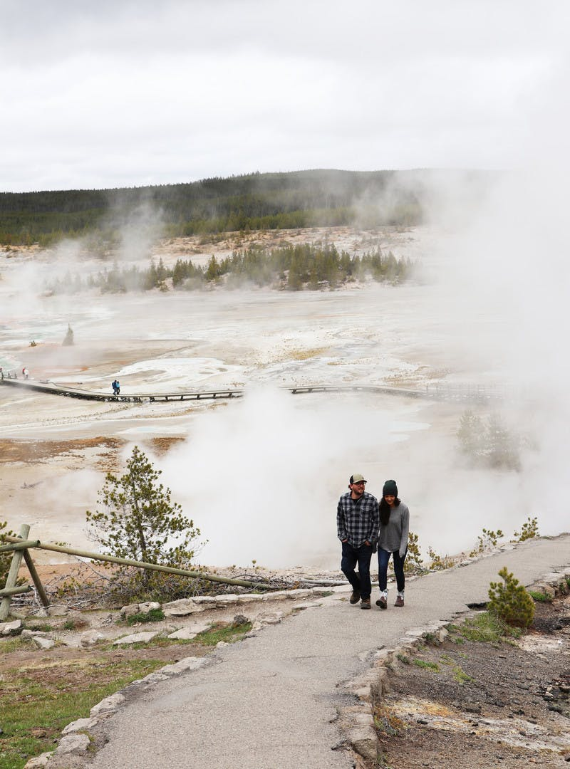 Juli and Jordan Cote walking down dirt path to steaming geysers in Yellowstone National Park.