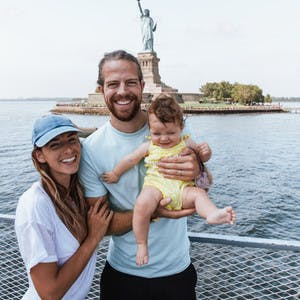 A family shot of Bryce Jurgy, his infant daughter and his wife, standing on a boat with the Statue of Liberty in the background.