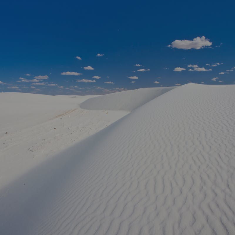 White sand dunes against blue sky at White Sands National Park