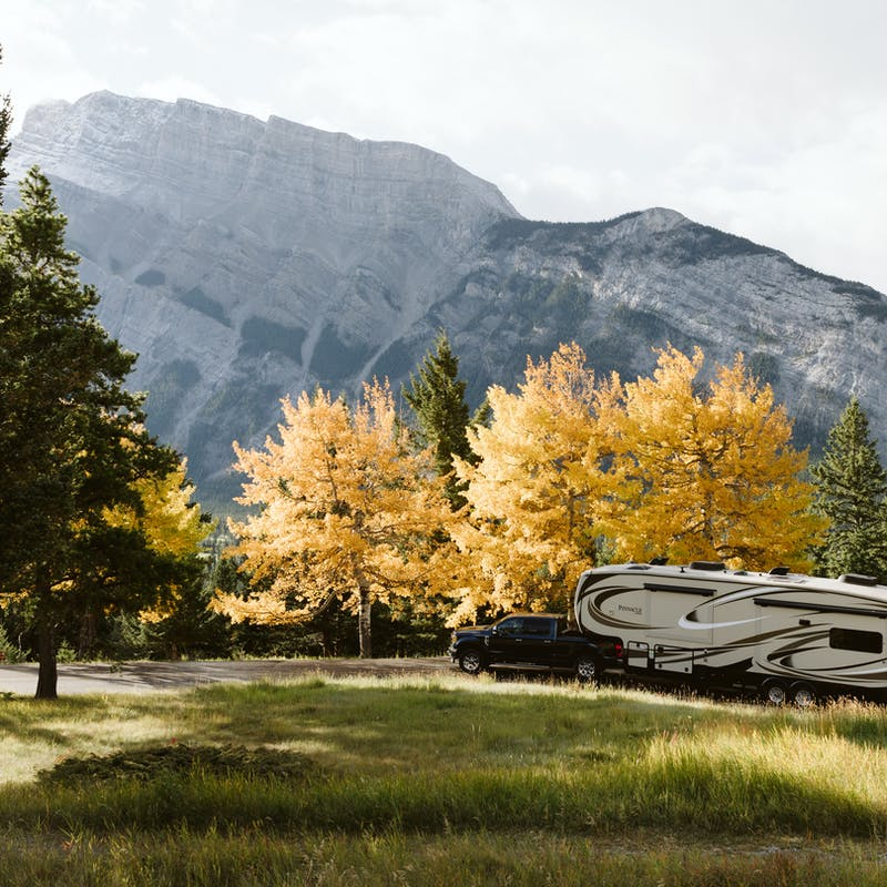A beautiful nature view with evergreens in the foreground, trees with golden leaves and a mountain in the background, and the truck pulling an RV parked in the middle.