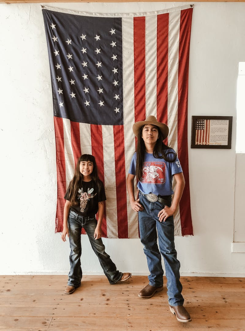 Two kids posed in front of an American flag display.