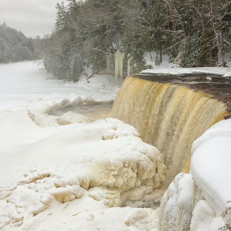 Wide waterfall with brownish colored water falling into a frozen and snow covered river, surrounded by snow
