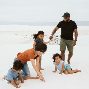 Jane and Willie Register, with their three kids, play in the sand at White Sands National Park in New Mexico.