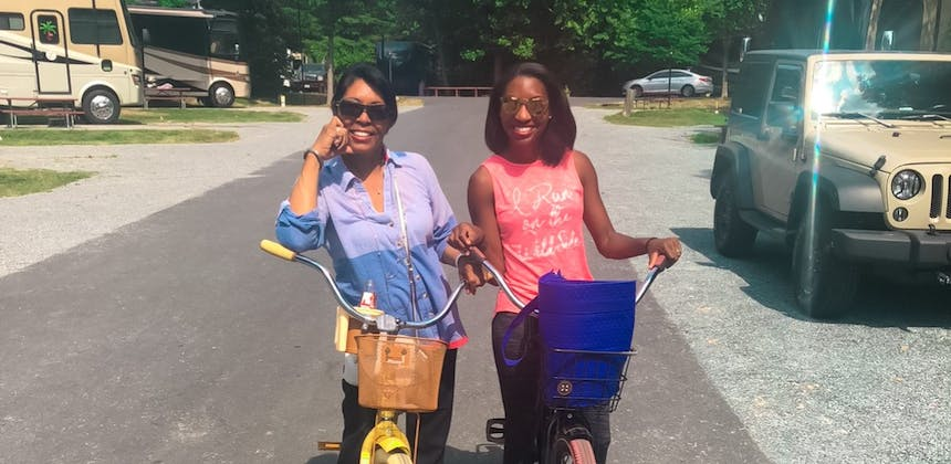 A mom and her daughter ride bikes in a campsite