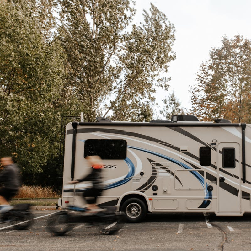 Dave and Kathy riding bikes in a whir past their parked RV.
