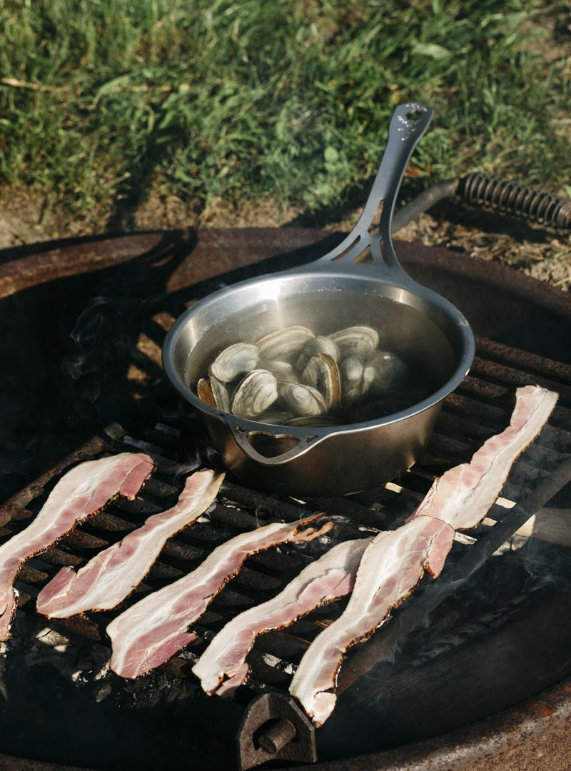 Bacon and clams cooking on a grill.