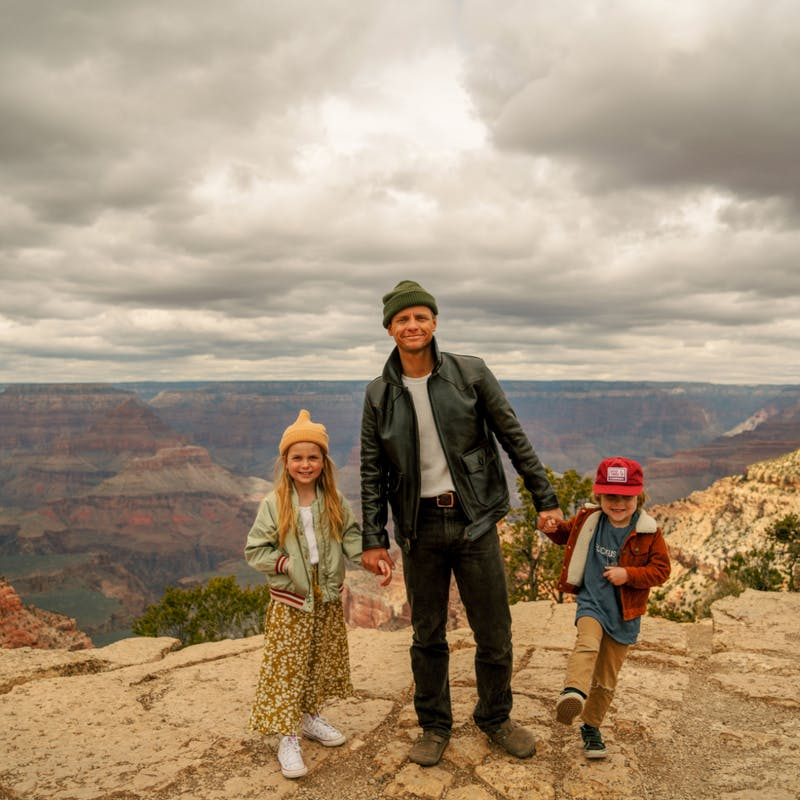 Man in hat holds hands of two young children in front of the Grand Canyon