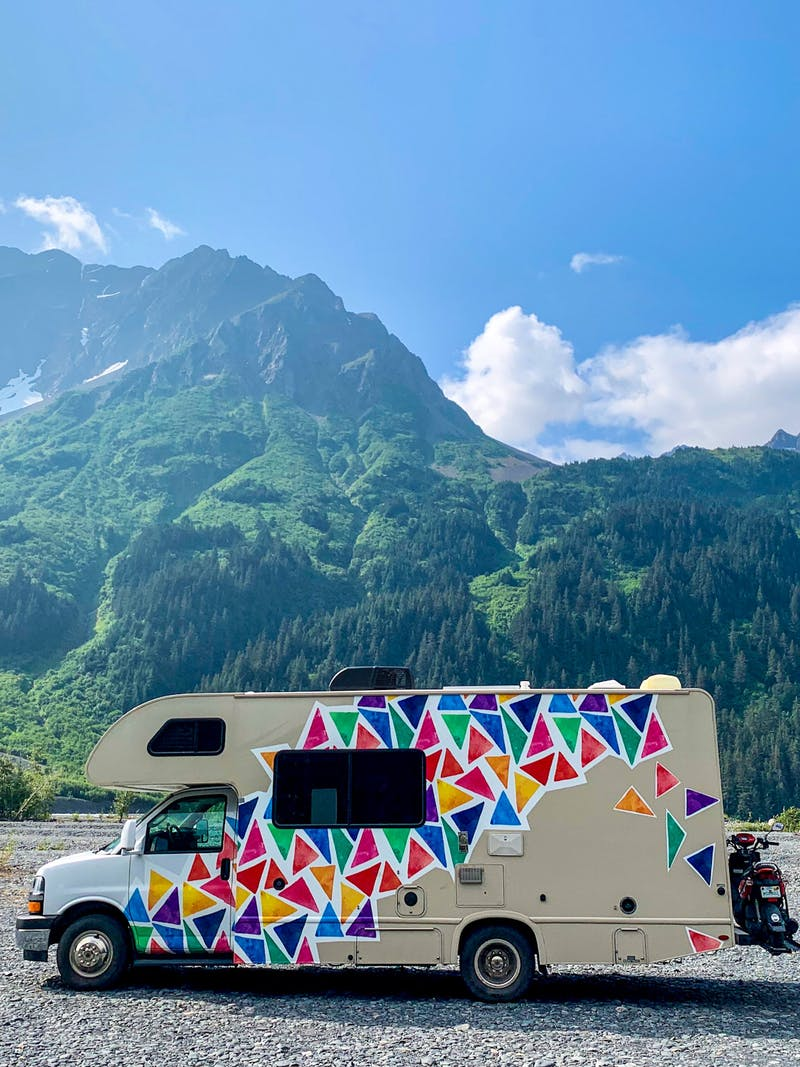 Jason and Dawn's Class C RV parked in a gravel lot near a large mountain.
