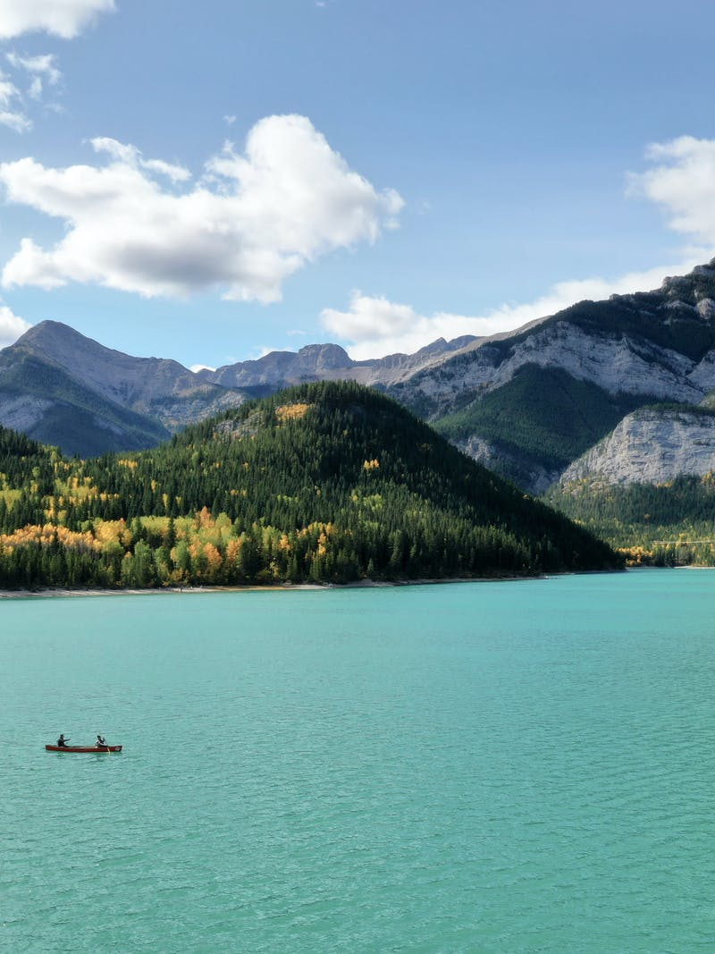 A couple kayaking on a pretty blue lake with mountains in the background.