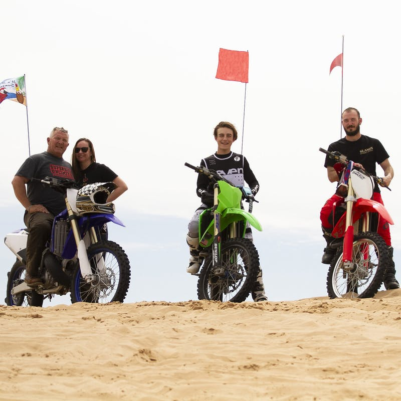 Four people posed on a dune with dirt bikes.