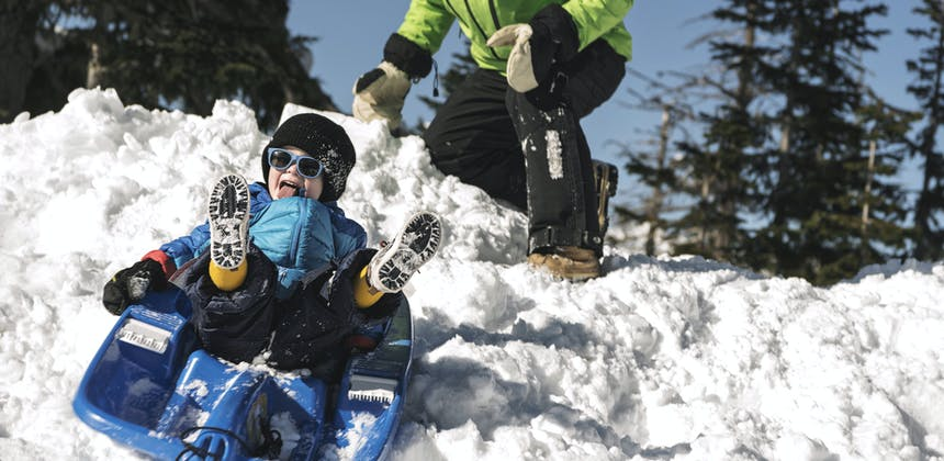 A young boy sleds down snow as his grandfather pushes him.