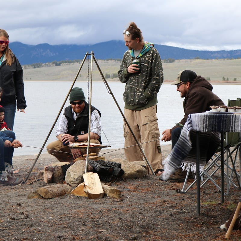 Group of five friends and one child stands around a campfire cooking hot dogs on a stick, with lake in the background.