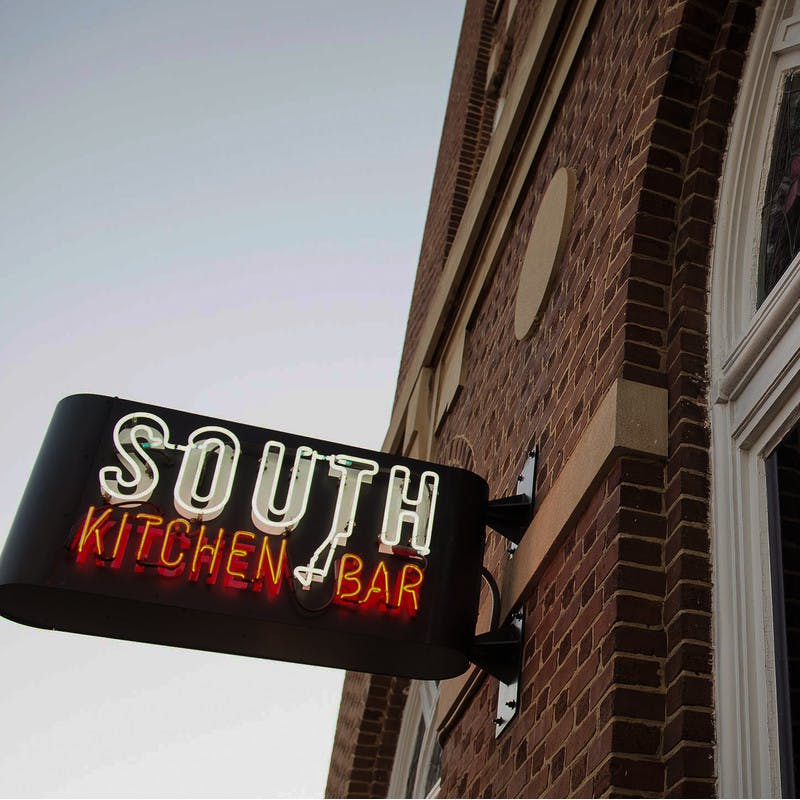 South Kitchen and Bar in Athens, Georgia restaurant brick exterior and front window with neon sign.