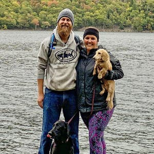 Kelsey and Scott Kiessig pose for the camera with their 2 dogs, while wearing sweatshirts, jackets, and winter hats in front of a body of water and trees.