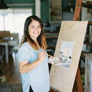 Coley Kuyper stands smiling in front of an easel, in a blue shirt, holding a paint brush and palette, painting a picture.