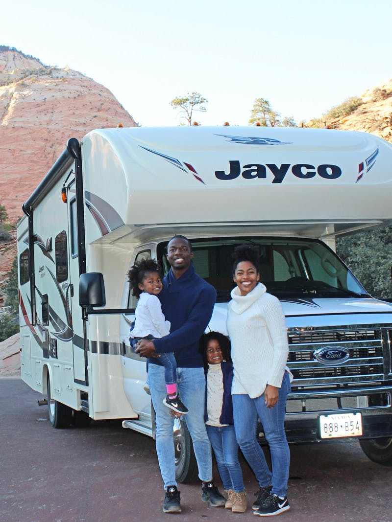 An African American family of 4 stands outside of their Jayco RV that is pulled off on the side of the road with the mountains and trees in the background.