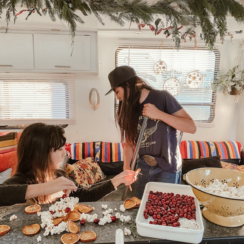 Two kids making Christmas garlands in an RV.