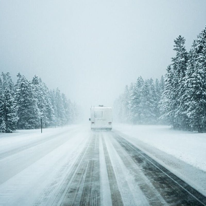 Back on Class C RV driving on snowy road surrounding by tall snowy pine trees