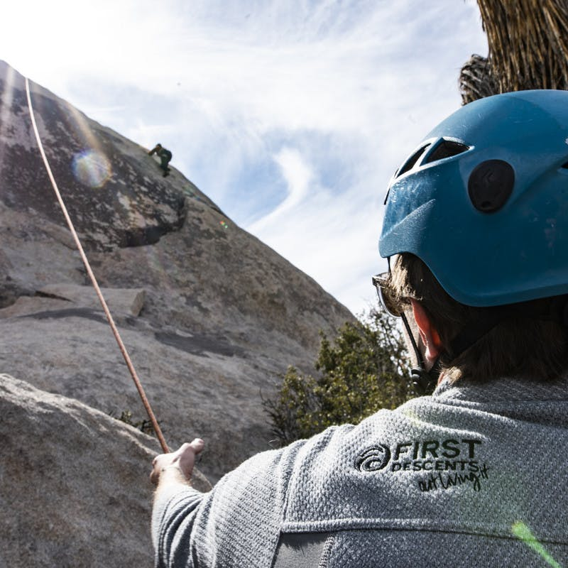 Volunteer wearing a First Descents jacket holds a climber's rope steady.