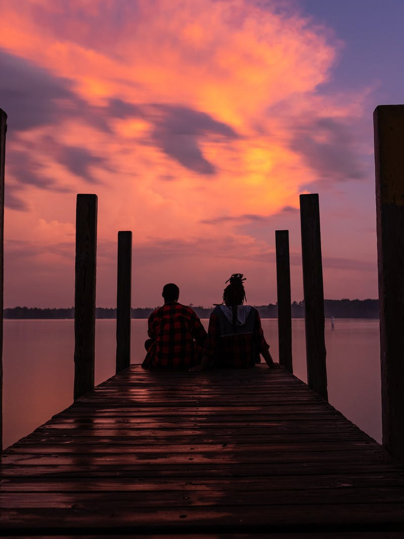 Chanel and Brittany Tate sitting on a dock watching the sunset.