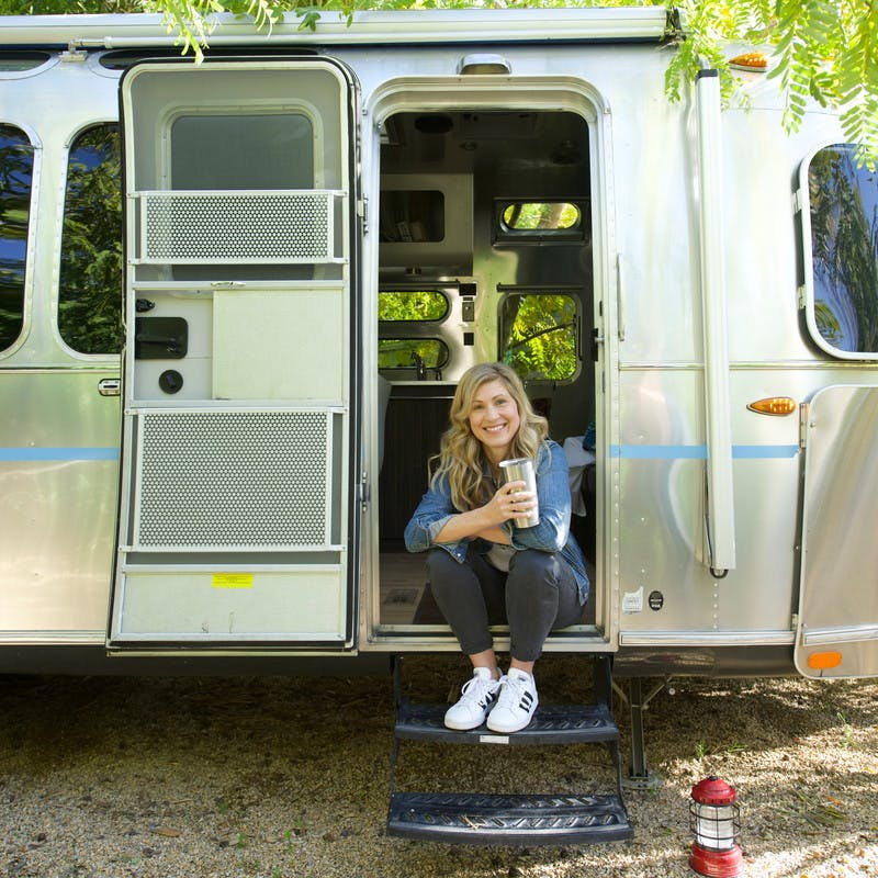 Image of Sarah Schulz sitting in the doorway of an Airstream travel trailer RV, smiling at the camera while holder a coffee cup.