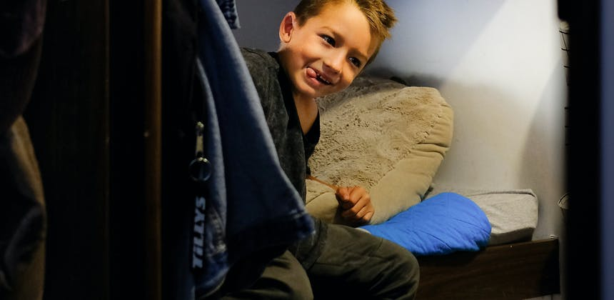 Two boys getting ready for bed in their bunk beds in an RV.