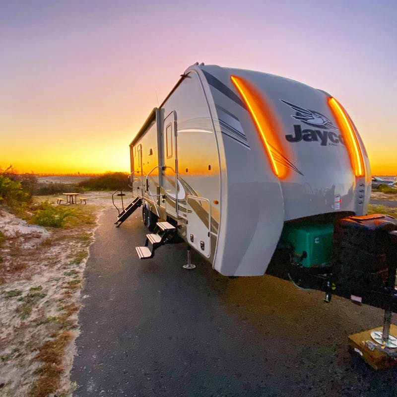 A Jayco RV trailer parked at a sandy campsite reflecting the sunrise.