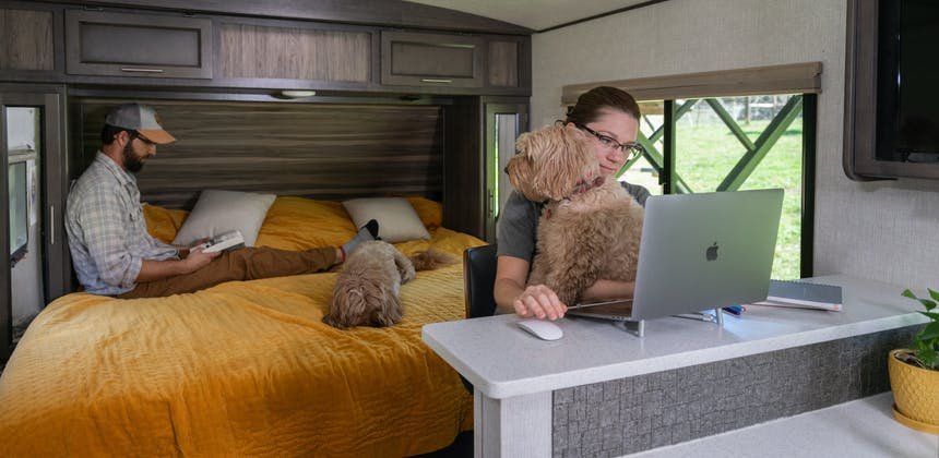 Marcia Schabel works at her computer while Todd reads sitting on the bed inside their Sunset Trail RV.