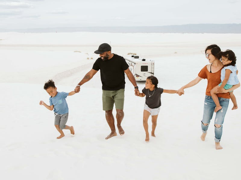 A family holds hands in front of an RV.