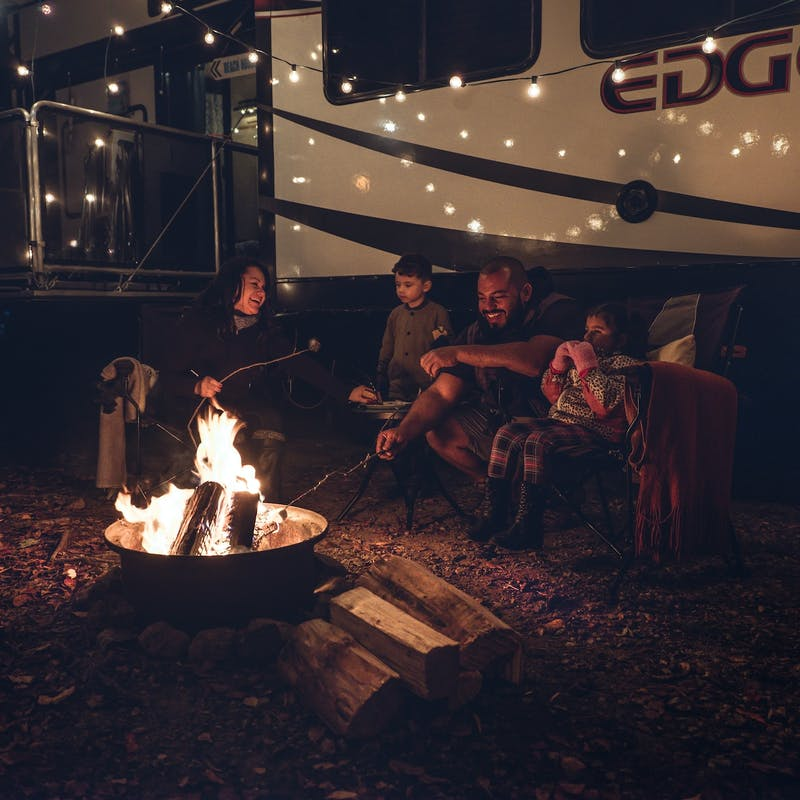 The Class Family gathered around a fire pit at night together.