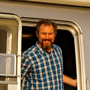 Greg Graham smiles while standing at the door of his Airstream.