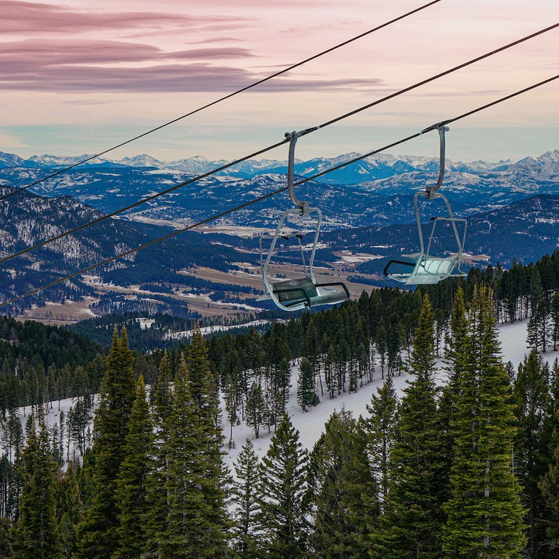 Ski lift chairs hanging above green pines and snowy mountains in the background with pink skies