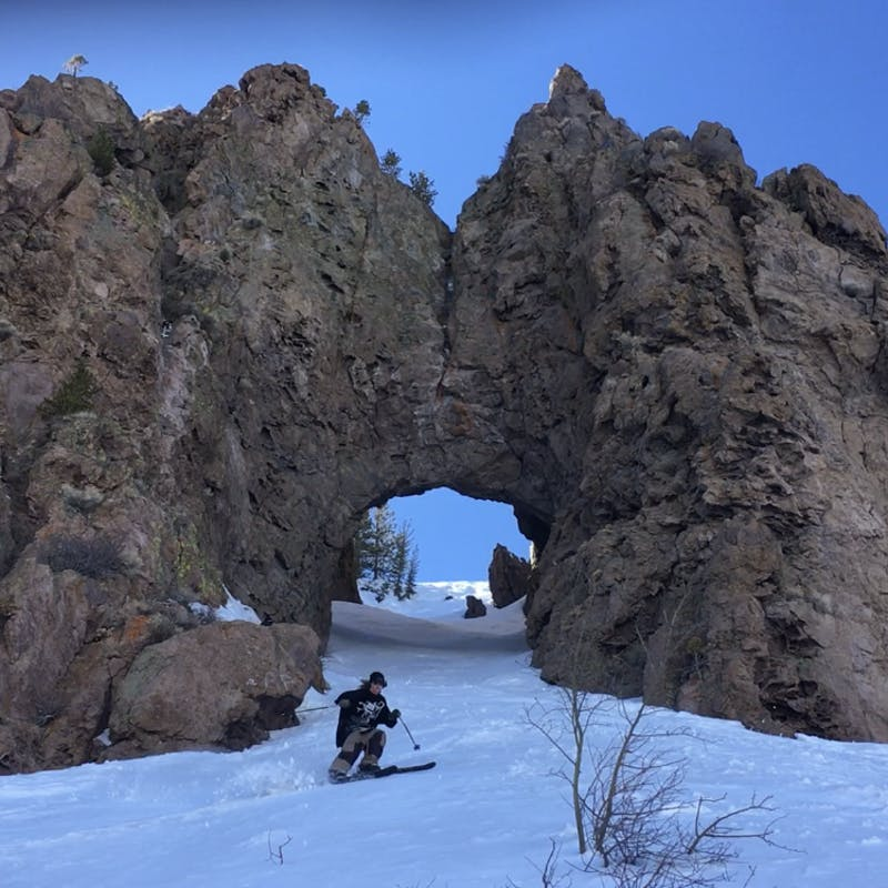 Ryan skiing through a stone cave that arches over the slope of the mountain.