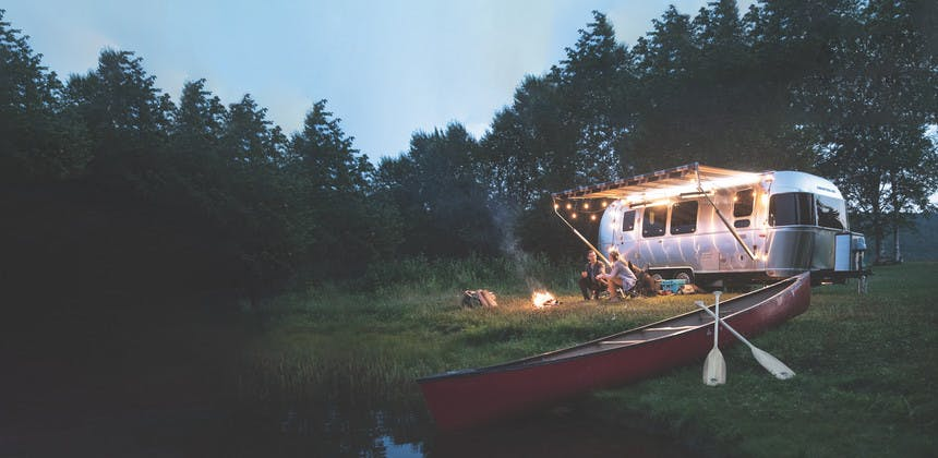 Airstream travel trailer RV on edge of lake with canoe, young couple sitting by camp fire with dog