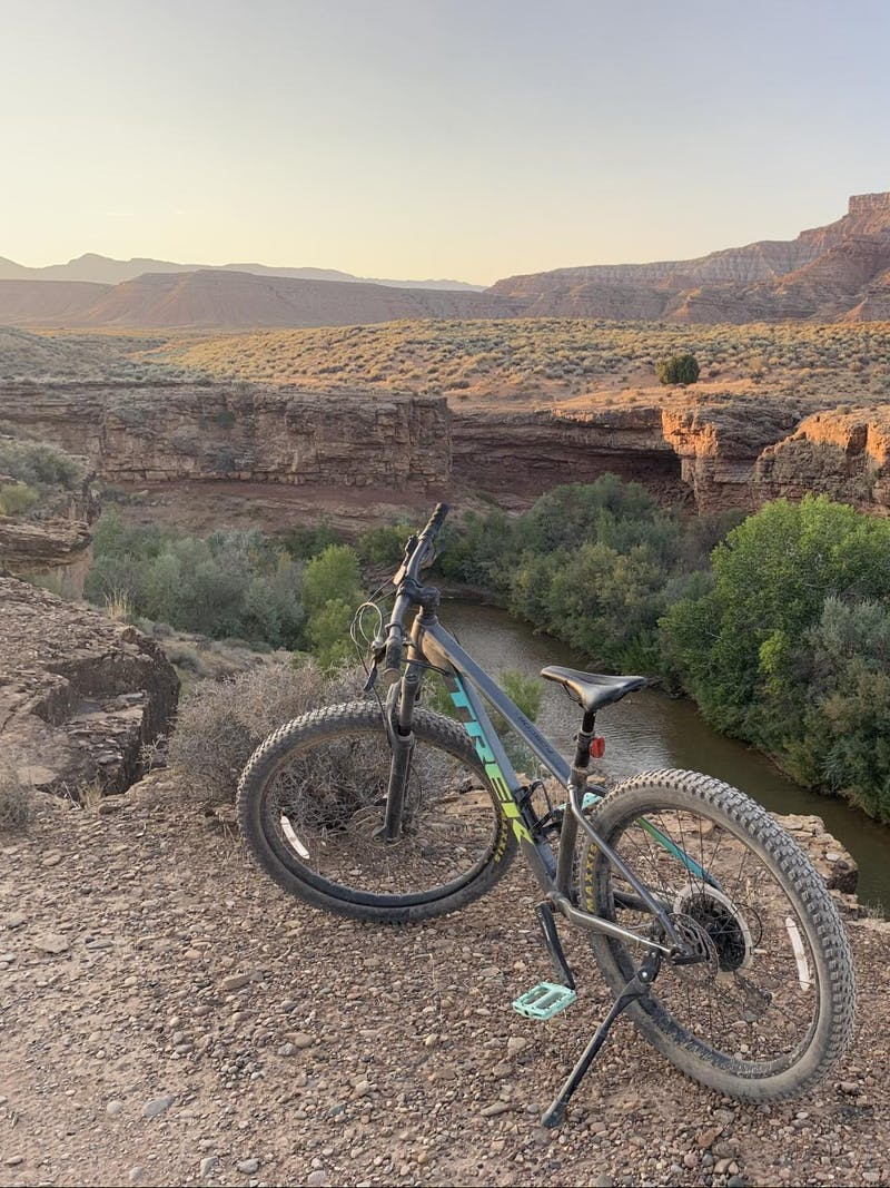 A bike sits on the edge of a cliff overlooking a river and mountains.