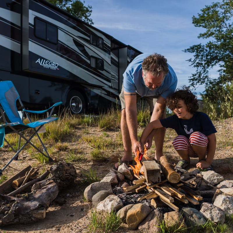 Desiree Walter's son and husband work on building a campfire with their Class A Allegro RV in the background.