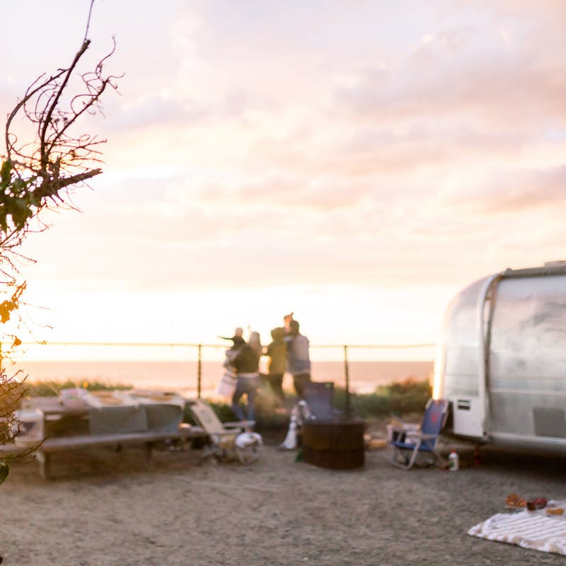 A wide shot of the Thrane family watching the sun set by a fence next to an Airstream Travel Trailer RV, with the beach & ocean in the background.