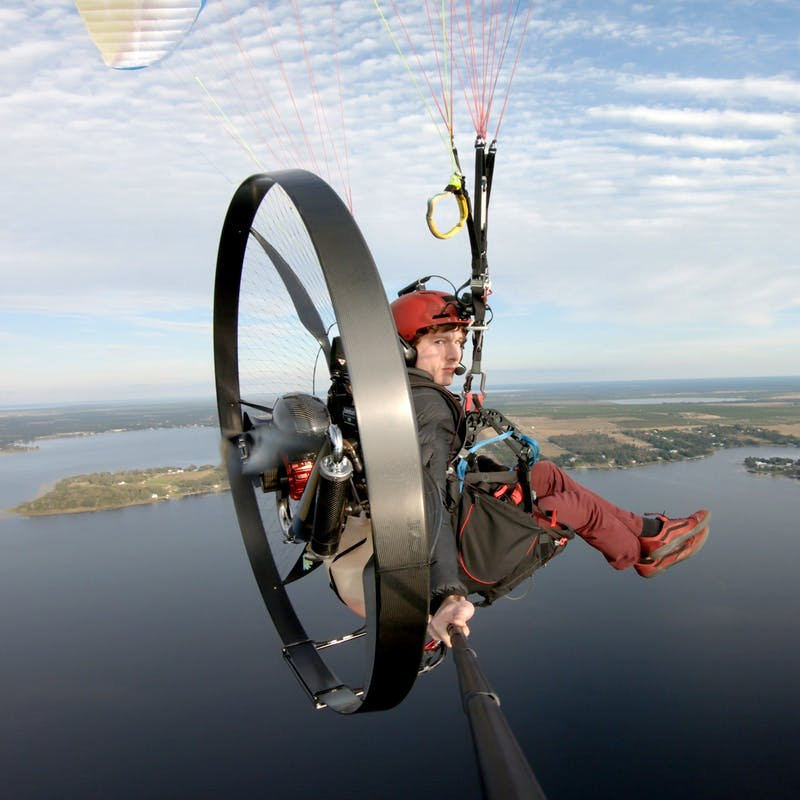 Tucker Gott takes a selfie while paramotoring over a lake.