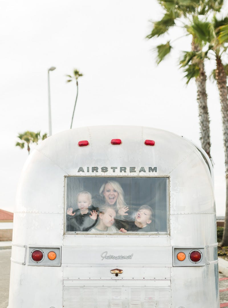 Amber Thrane with three kids, looking out the back window of Airstream RV, with palm trees in the background.