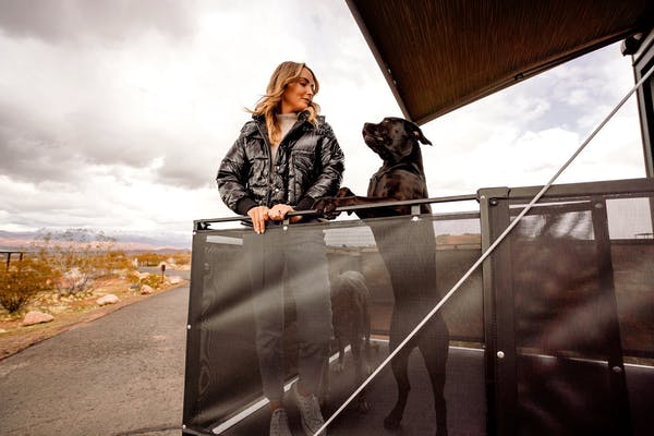 A woman stand on the porch of a toy hauler RV with her dog.