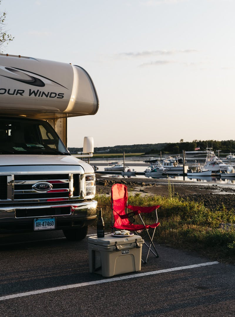 Exterior RV shot alongside a marina with folding chair, Yeti cooler, and beer.