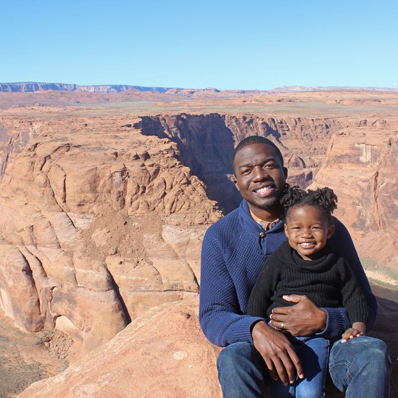 An African American father and daughter smile at the camera while sitting in front of Horseshoe Bend.