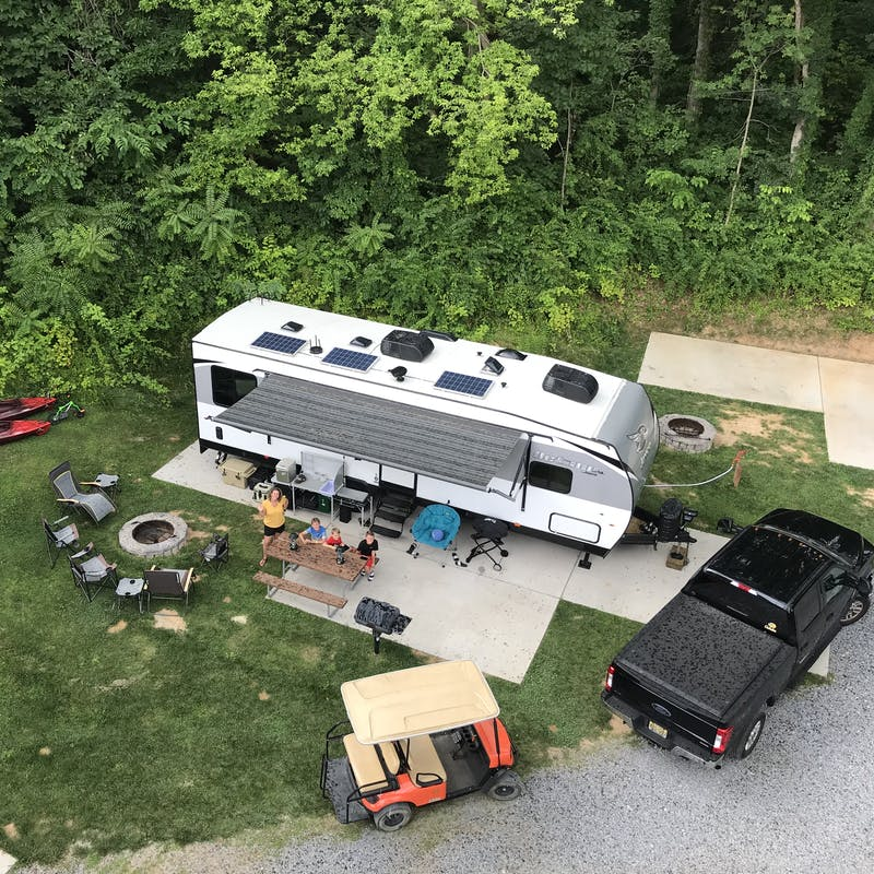 An aerial shot of an RV parked at an idyllic campground.